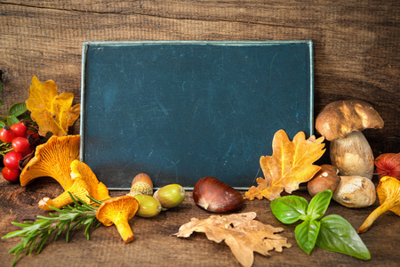 blackboard background: Thanksgiving still life with mushrooms, seasonal fruit and vegetables on wooden table with space for text.  Cooking concept Stock Photo