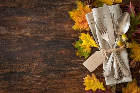 decoracion mesas: Acci�n de Gracias ajuste con cubiertos y arreglo de coloridas hojas de oto�o lugar oto�o Foto de archivo