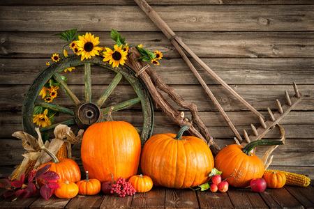 Thanksgiving herfststilleven met pompoenen en oud houten wiel