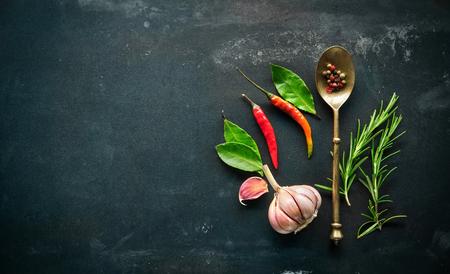 pepe nero: Erbe e spezie con vecchio cucchiaio di metallo su sfondo di ardesia