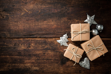 holiday backgrounds: Christmas gift boxes and decoration over grunge wooden background Stock Photo