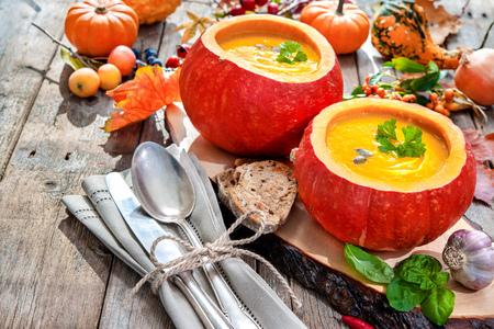 party table: Pumpkin soup in the open pumpkins on a wooden table