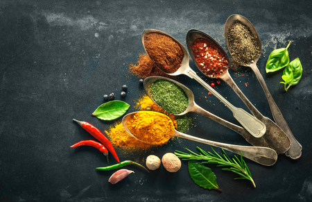 Various herbs and spices on black stone plate Foto de archivo