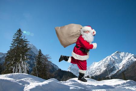 De Kerstman loopt met de zak van de cadeautjes Stockfoto - 46316120