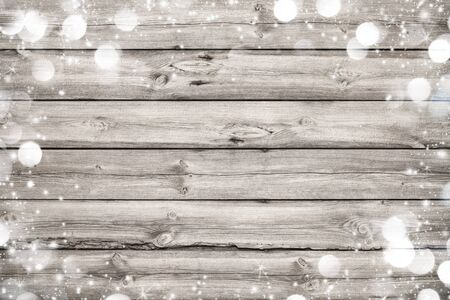 holiday celebration: Christmas frame on wooden background with snow and lights Stock Photo