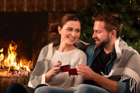 parejas amor: Pareja de relax con un vaso de vino en la romántica chimenea en noche de invierno Foto de archivo