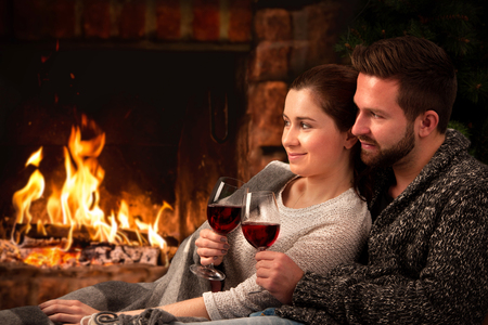 lodges: Couple relaxing with glass of wine at romantic fireplace on winter evening