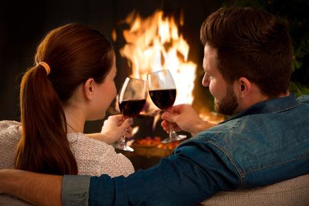 anochecer: Pareja de relax con un vaso de vino en la romántica chimenea en noche de invierno Foto de archivo