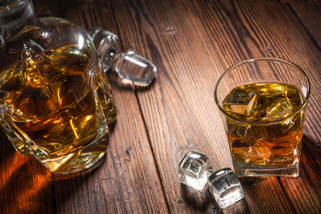 old desk: Glasses of whiskey with ice on wooden table