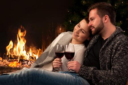 vin chaud: Couple de d�tente avec un verre de vin � la chemin�e romantique le soir d'hiver