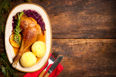 christmas dish: Crusty goose leg with braised red cabbage and dumplings. Cooking at Christmas time Stock Photo