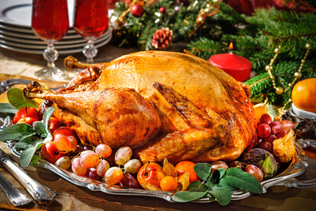 christmas cooking: Roasted turkey on holiday table with candles Stock Photo