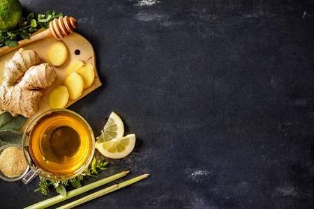 taza de té: Taza de té de jengibre con limón y miel en la placa de pizarra