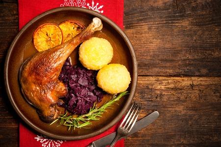 Knapperig gans been met gestoofde rode kool en knoedels. Koken in de kersttijd Stockfoto