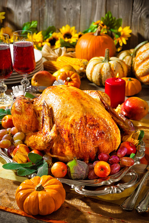 feasts: Thanksgiving dinner. Roasted turkey on holiday table with pumpkins, flowers and wine