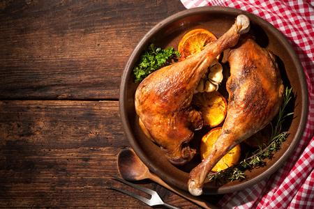 feasts: Roasted goose legs with oranges and spices. Cooking at Christmas time Stock Photo