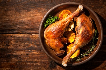 roast turkey: Roasted goose legs with oranges and spices. Cooking at Christmas time Stock Photo