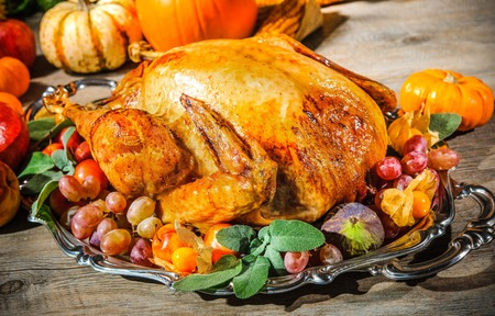 thanksgiving feast: Thanksgiving dinner. Roasted turkey on holiday table with pumpkins, flowers and wine