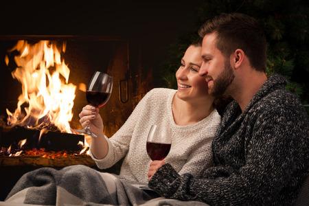 jovenes tomando alcohol: Pareja de relax con un vaso de vino en la romántica chimenea en noche de invierno Foto de archivo