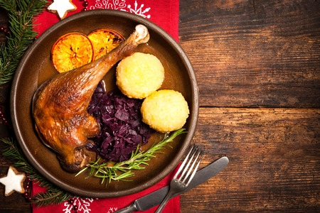 Crusty goose leg with braised red cabbage and dumplings. Cooking at Christmas time Standard-Bild