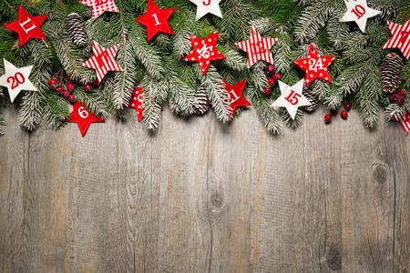 calendrier: Branches de sapin et calendrier de l'avent étoiles sur vieille planche de bois