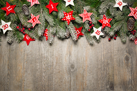 Fir tree  branches and advent calendar stars on old wooden board Stock Photo