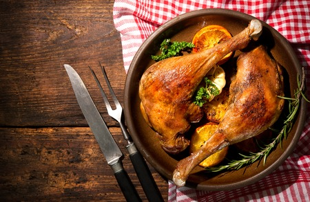 baked chicken: Roasted goose legs with oranges and spices. Cooking at Christmas time Stock Photo