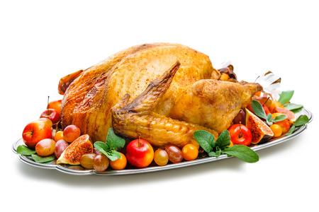 Garnished roasted turkey on platter over white background Foto de archivo