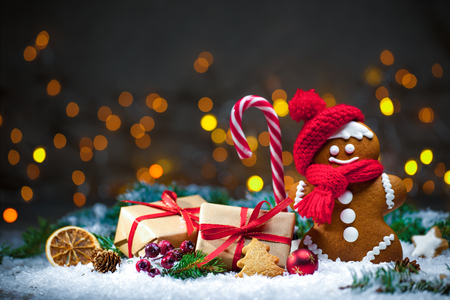 Gingerbread man with Christmas presents in snow Imagens