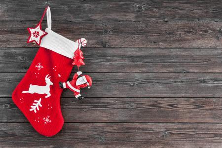 madera r�stica: Decoraci�n de la media y los juguetes de Navidad colgando sobre fondo de madera r�stica