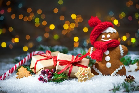 Gingerbread man with Christmas presents in snow Stock Photo