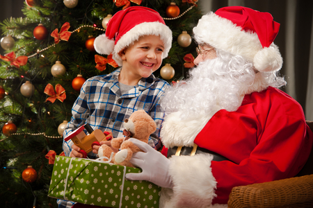 obtain: Santa Claus and a little boy in conversation in front of Christmas Tree