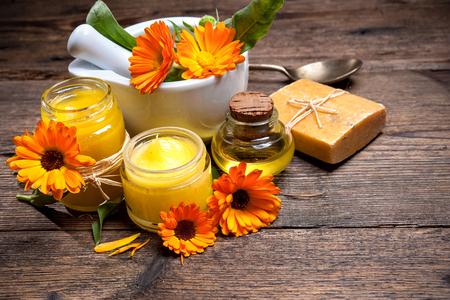 flores secas: Pomada de caléndula casera, jabón y aceite en la mesa de madera