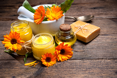 Homemade calendula ointment, soap and oil on wooden table Stockfoto