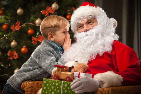 Santa Claus and a little boy. Boy tells wishes in front of Christmas Tree