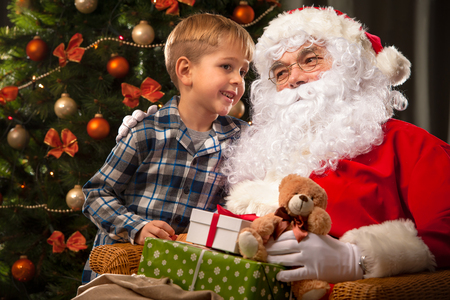 2 year old: Santa Claus and a little boy. Boy tells wishes in front of Christmas Tree