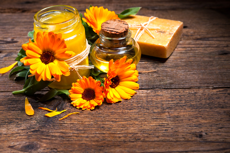 ointment: Homemade calendula ointment, soap and oil on wooden table Stock Photo