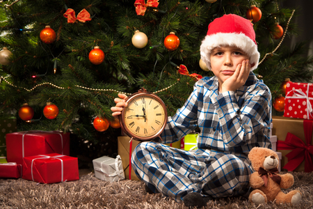in pajama: Little boy in pajama with the alarm clock waiting impatiently for Santa Stock Photo