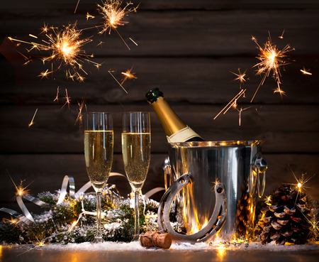 New Years Eve celebration background with pair of flutes and bottle of champagne in bucket and a horseshoe as lucky charm Stock Photo - 50199414