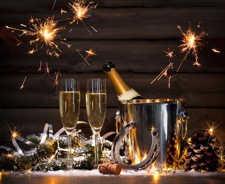 Silvester Feier Hintergrund mit zwei Flöten und Flasche Champagner im Eimer und ein Hufeisen als Glücksbringer