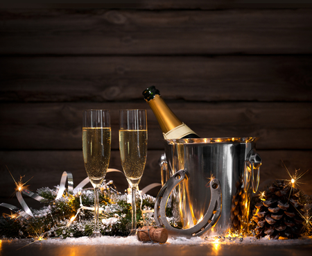new year s eve: New Years Eve celebration background with pair of flutes and bottle of champagne in bucket and a horseshoe as lucky charm