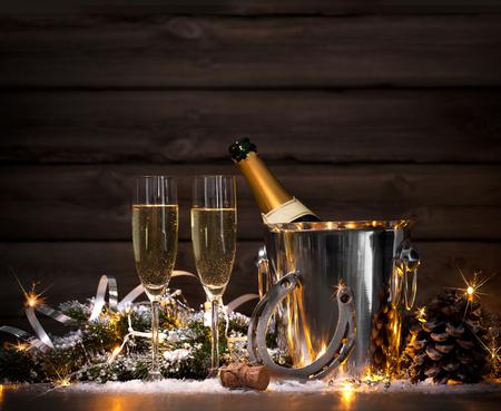 herradura: Nochevieja fondo de la celebración con pares de flautas y botella de champán en un cubo y una herradura como amuleto de la suerte