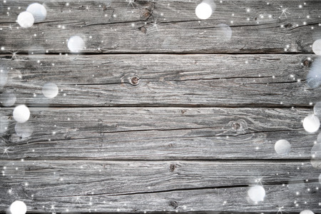 new year: Christmas background with falling snow and lights over weathered wood