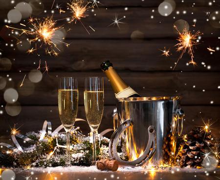 New Year: Sylwester uroczystość tła z parą flety i butelka szampana w wiaderku i podkowy jako talizman