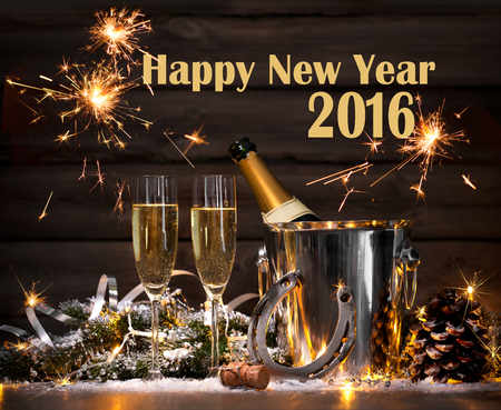 lucky charm: New Years Eve celebration background with pair of flutes and bottle of champagne in bucket and a horseshoe as lucky charm