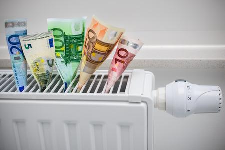 お金でサーモスタットを加熱、高価な暖房費用の概念