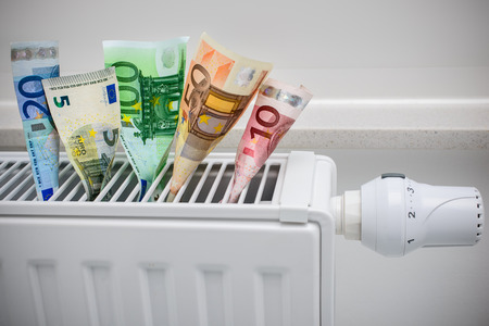 heating thermostat with money, expensive heating costs concept Standard-Bild