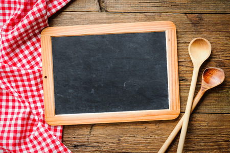 wooden table top view: Wooden spoon on a blackboard with a red checkered tablecloth