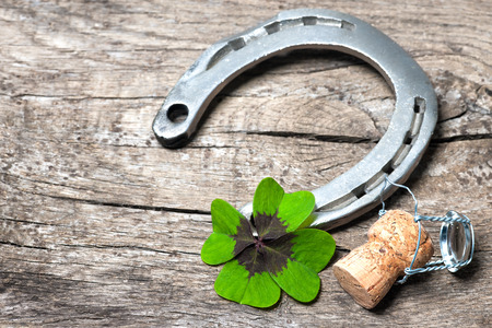 shamrock: Horseshoe, shamrock and champagne cork on old wooden
