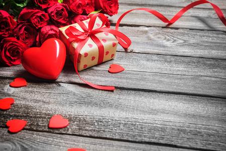 Fondo del día de San Valentín de la vendimia con el corazón, rosas rojas y caja de regalo sobre tabla de madera
